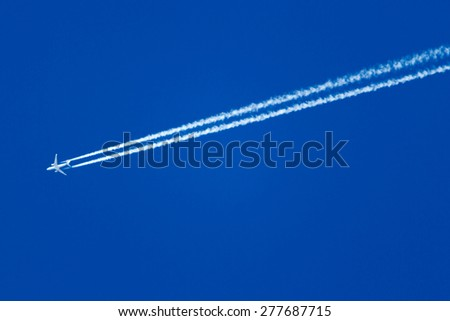jet plane in the blue sky, the trace of the Turbines - stock photo
