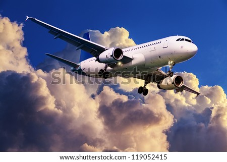 Jet plane is maneuvering for landing in a sunset sky - stock photo