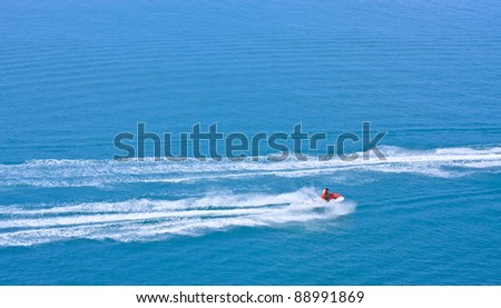 jet-ski racing on a blue water and blue sky as background - stock photo
