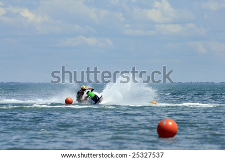 Jet Ski rider maneuvers around a buoy in competition. - stock photo
