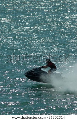 jet-ski rider skimming the waves at speed - stock photo