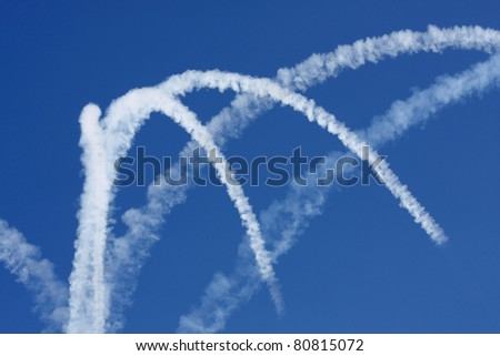 Jet trails against a dark blue sky