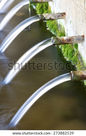 Jets of water coming through the pipes of an old fountain, Pnarroya de Tastavins, Teruel, Aragon, Spain. - stock photo
