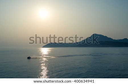 Jetski going fast in the calm sea with mountain range silhouettes at the background. Evening agains? the sun photo. Montenegro. - stock photo