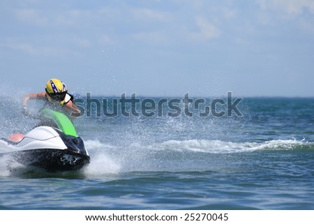 Jetski rider maneuvers around a buoy in competition. - stock photo