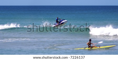 jetskier jumps out of surf wave into air while kayaker looks on