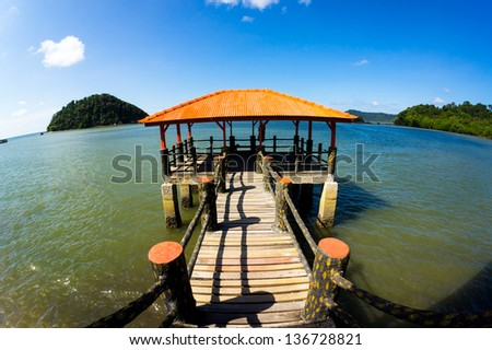 Jetty and ocean with blue sky - stock photo