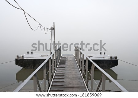 Jetty at foggy morning with water and reflection