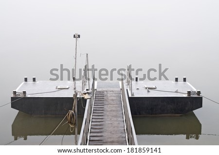 Jetty at foggy morning with water and reflection - stock photo