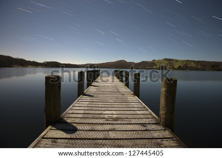jetty at night with star trails - stock photo