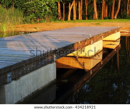 Jetty at the shore, sunset st the lake - stock photo