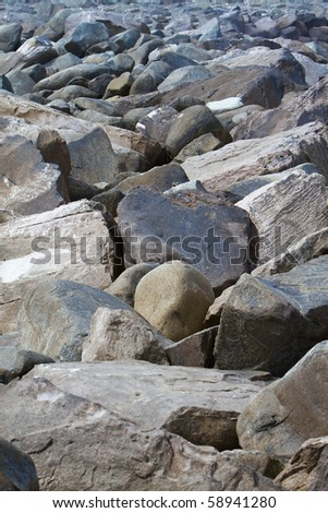 Jetty breaker boulders of large rocks to protect bay - stock photo