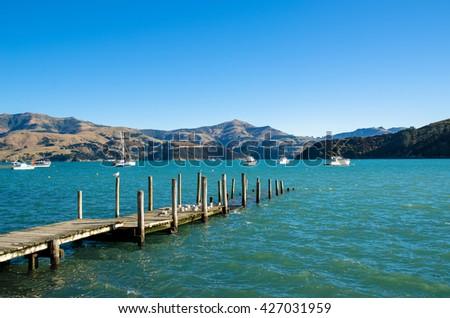 Jetty in Akaroa, south island of New Zealand. - stock photo