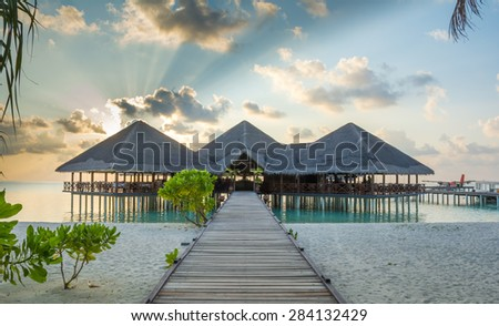 Jetty leading to overwater resort hotel restaurant and arrival - stock photo