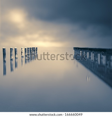 Jetty on a lake with dramatic sky - stock photo
