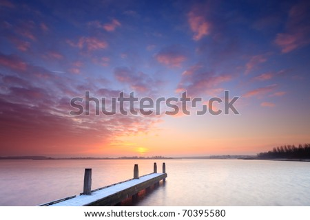Jetty on lake at sunset - stock photo