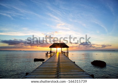 Jetty silhouette against beautiful sunset in Mauritius Island - stock photo