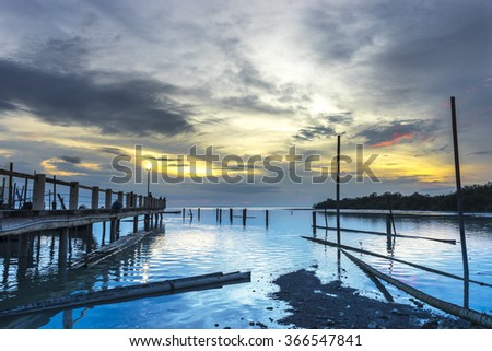 Jetty silhouette with sunset background - stock photo