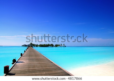 jetty that leads to an tropical island on the maldives - stock photo