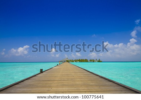 jetty to tropical island with palm trees and blue sly; Maldives - stock photo