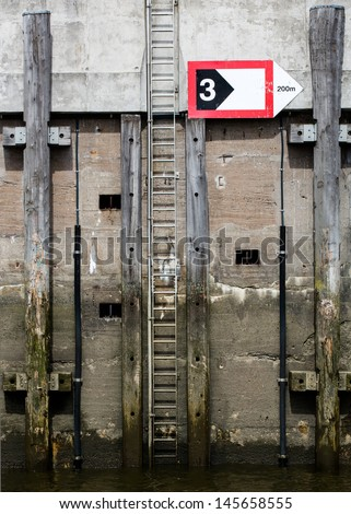 jetty with a ladder and a sign at the harbor of Hamburg (Germany) - stock photo
