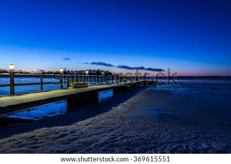 Jetty with lights during sunset a winter night