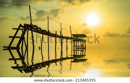 Jetty with reflection and sunset background - stock photo