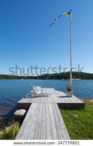Jetty with sunbeds, flagpole and views of the sea on the island Yxlan in the Swedish archipelago in the Baltic Sea off Stockholm - stock photo
