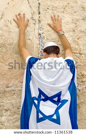 Jew covered by flag praying in the wailing wall in Jerusalem.