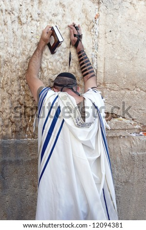 Jew in tallith prays in the western wall in Jerusalem. - stock photo