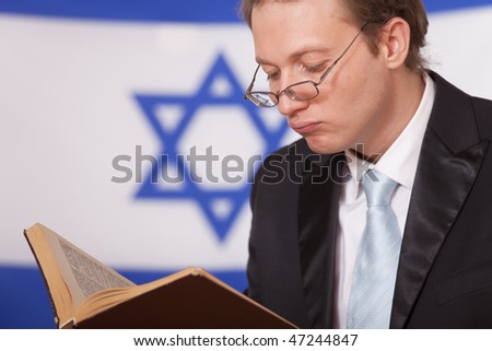 jew reading book in front of israel flag - stock photo