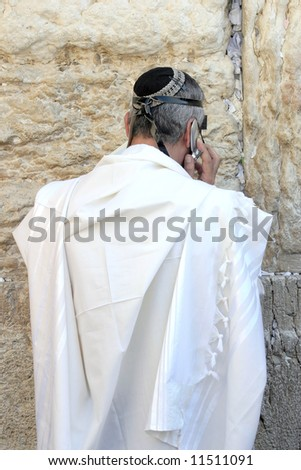 Jew speaks on the cell phone in the wailing wall in Jerusalem. - stock photo