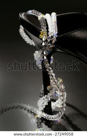 jewel necklace around a fashion black shoe heel on dark background - stock photo