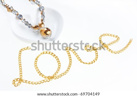 "Jewel necklace on heart shaped saucer and yellow metal chain arranged in form of word ""Love"" - stock photo"