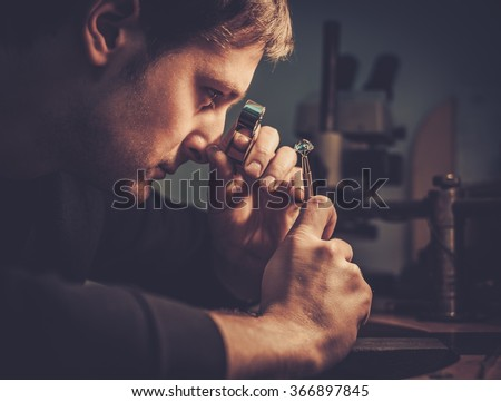 Jeweler looking at the ring through microscope in a workshop. - stock photo