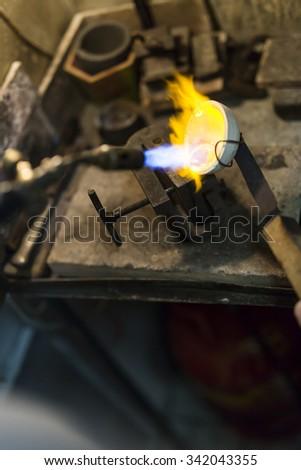 Jeweler melting gold and making jewelry - stock photo