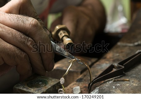 Jeweler melting gold bracelet with gasoline burner for making jewelry - stock photo