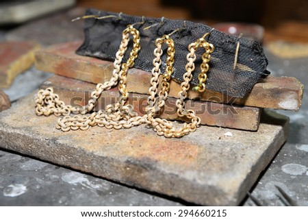 jeweler produces gold jewelry in the workshop - stock photo
