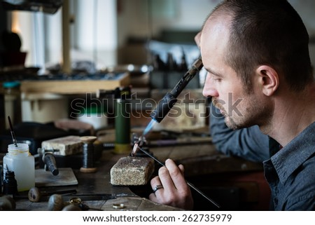 Jeweler silver soldering in his workshop. - stock photo
