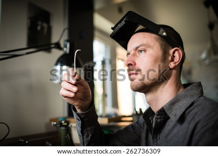 Jeweler working on unfinished ring in his workshop. Craft jewelery making. - stock photo