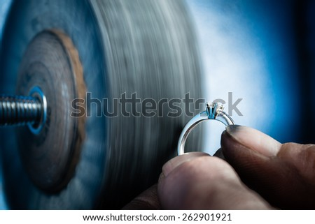 Jeweler working on wedding gold ring in his workshop. Detail of silver polishing. - stock photo