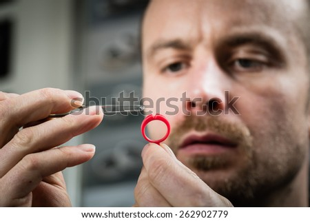 Jeweler working with wax model ring in his workshop. Craft jewelery making. Detail shot with low depth of field. - stock photo