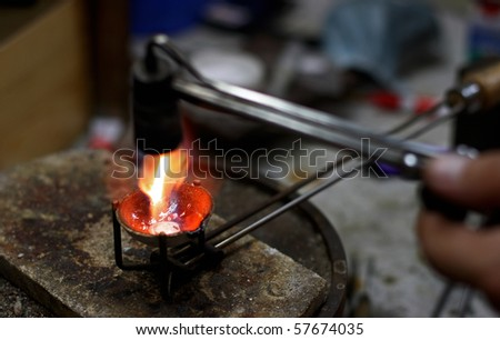 Jewelers manufacture. Melting silver in a small crucible for making jewelery - stock photo