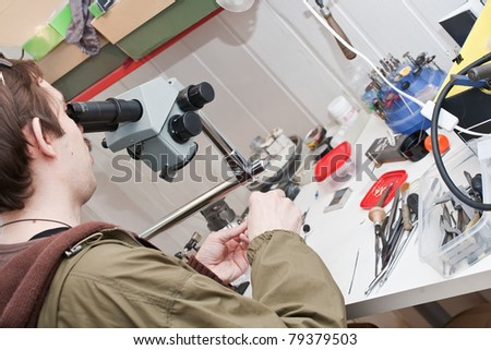 jeweller is working with  microscope at jeweller's workshop