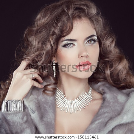 Jewelry and Fashion elegant lady. Beautiful Woman wearing in Luxury Fur Coat over black background. - stock photo