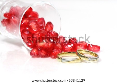 Jewelry and Food Series: pomegranate seeds and marriage rings, macro, high-key. - stock photo
