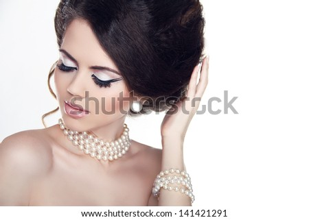 Jewelry and Makeup. Fashion portrait of beautiful woman with pearls isolated on white background. - stock photo