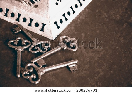 Jewelry box and four vintage keys. Four vintage keys. Retro aged toned photo with scratches. Sepia. - stock photo