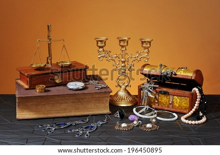 Jewelry boxes, books and candlestick on the table - stock photo