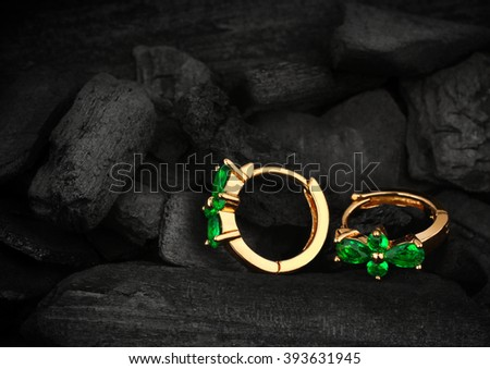 jewelry earrings witht gem emerald on dark coal background
